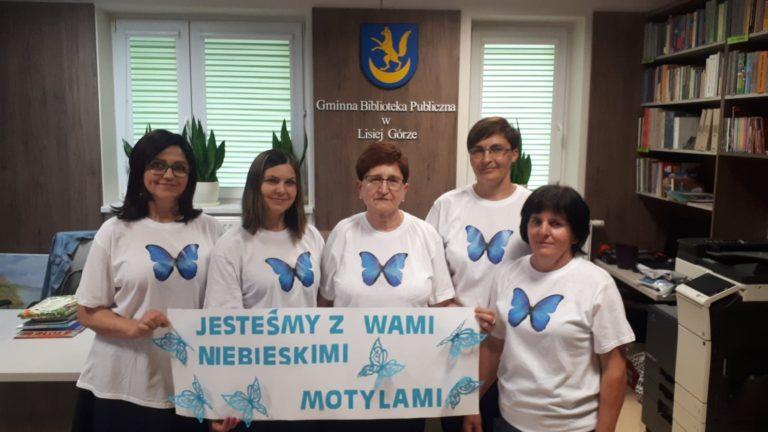 """osoby wbiałych koszulkaxh znadrukowanych nanich niebieskimi motylami, trzymające napis """"jesteśmy zwami niebieskimi motylami"""