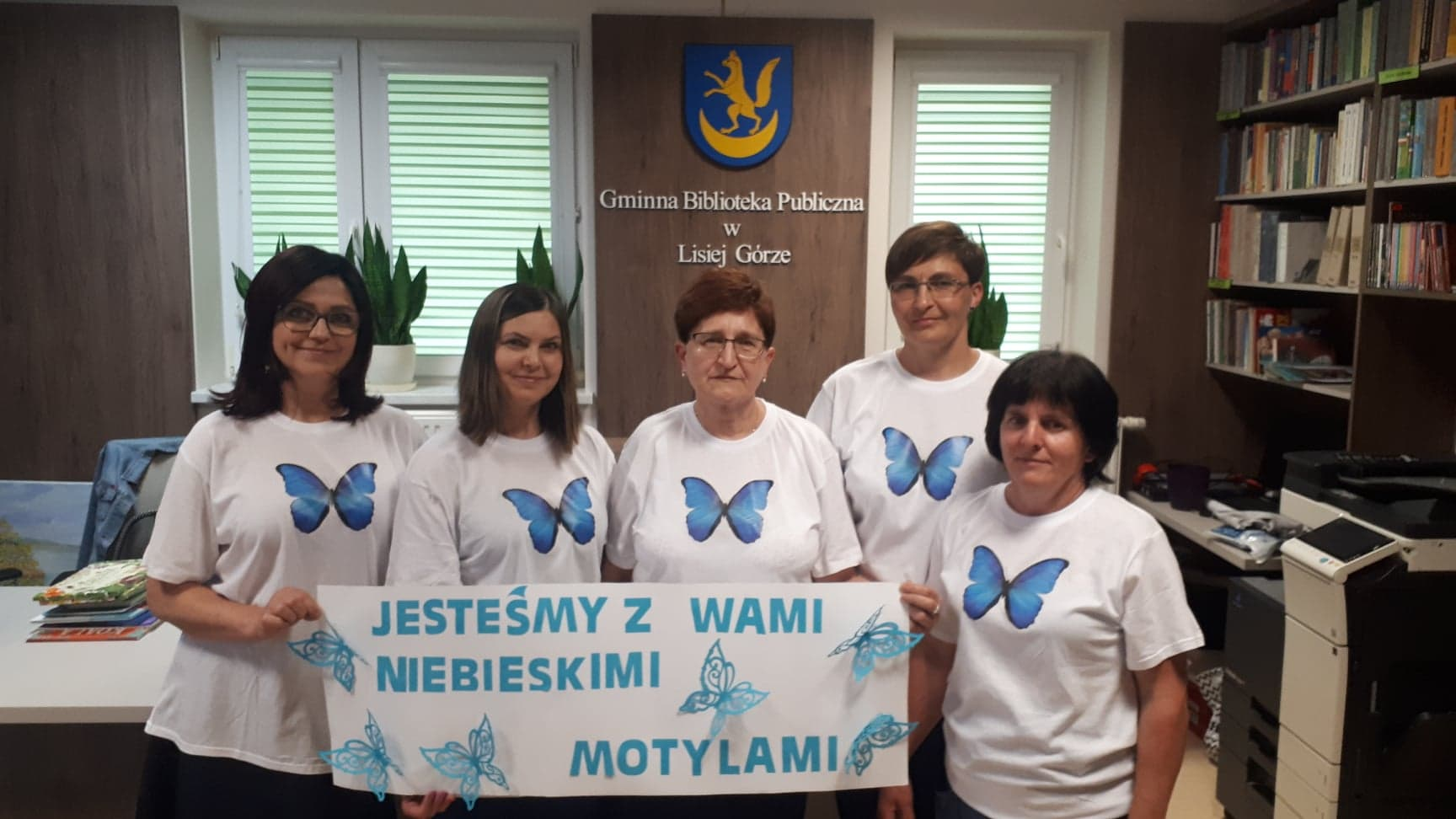"""osoby w białych koszulkaxh z nadrukowanych na nich niebieskimi motylami, trzymające napis """"jesteśmy z wami niebieskimi motylami"""